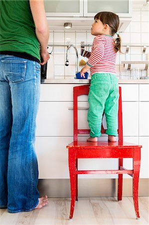 Full length of girl looking at mother while standing on chair in kitchen Stock Photo - Premium Royalty-Free, Code: 698-08226734