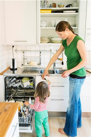 Full length mother taking spoon from little daughter in kitchen Stock Photo - Premium Royalty-Free, Code: 698-08226739