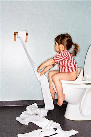 Side view of girl removing paper while sitting on toilet Stock Photo - Premium Royalty-Free, Code: 698-08226733