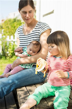 Woman with baby looking at girl eating banana outdoors Stock Photo - Premium Royalty-Free, Code: 698-08226742