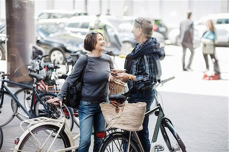Happy senior couple with bicycles standing on city street Stock Photo - Premium Royalty-Free, Code: 698-08226767