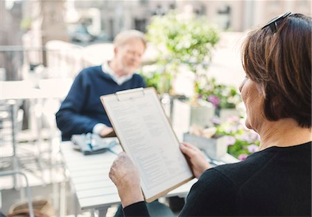 Rear view of woman reading menu while man sitting at sidewalk cafe Stock Photo - Premium Royalty-Free, Code: 698-08226779