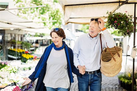 Happy senior couple walking at flower market Stock Photo - Premium Royalty-Free, Code: 698-08226787