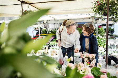Happy senior couple talking while buying flowers at market Stock Photo - Premium Royalty-Free, Code: 698-08226793