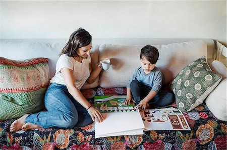 Mother assisting son in doing homework on sofa Stock Photo - Premium Royalty-Free, Code: 698-08226836