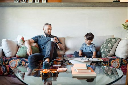 Father holding coffee mug while assisting son in doing homework at home Stock Photo - Premium Royalty-Free, Code: 698-08226837