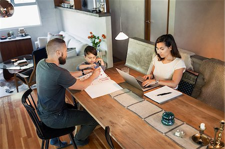 Mother working on laptop while father assisting son in doing homework at dining table Stock Photo - Premium Royalty-Free, Code: 698-08226842