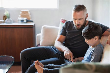 father with two sons not girls - Father assisting son in using digital tablet on sofa at home Stock Photo - Premium Royalty-Free, Code: 698-08226855