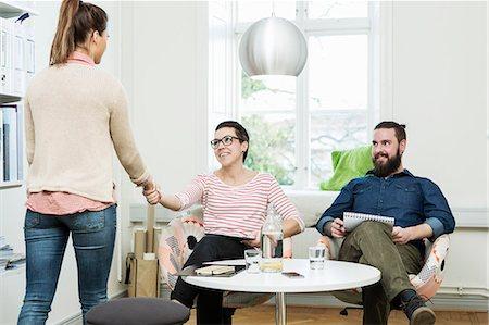 Businesswomen shaking hands in creative office Stock Photo - Premium Royalty-Free, Code: 698-08226868