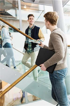 Low angle view of man giving book to friend in university Stock Photo - Premium Royalty-Free, Code: 698-08330619