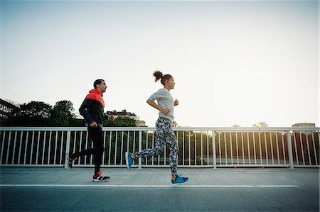 female - Man and woman running on sidewalk against clear sky Stock Photo - Premium Royalty-Free, Code: 698-08330702