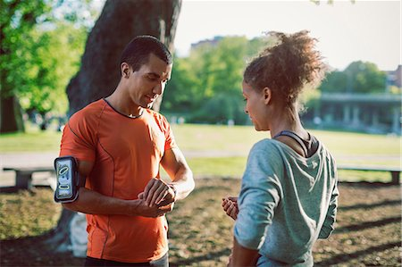 stop watch - Man showing wristwatch to female friend while standing in park Stock Photo - Premium Royalty-Free, Code: 698-08330749