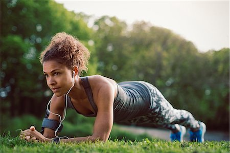 Sporty woman doing plank exercise at park Stock Photo - Premium Royalty-Free, Code: 698-08330767