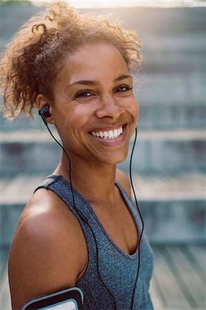 Portrait of smiling woman wearing headphones and standing at park Stock Photo - Premium Royalty-Free, Code: 698-08330778