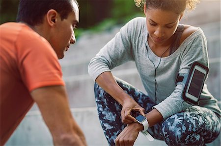Woman looking at smart watch while friend doing push-ups Stock Photo - Premium Royalty-Free, Code: 698-08330782