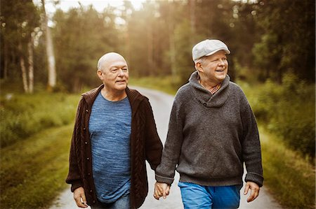 Happy gay couple looking away while walking on road amidst trees Stock Photo - Premium Royalty-Free, Code: 698-08330846