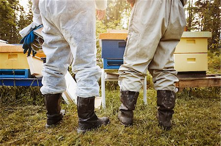 Low section rear view of beekeepers standing on field Stock Photo - Premium Royalty-Free, Code: 698-08330858