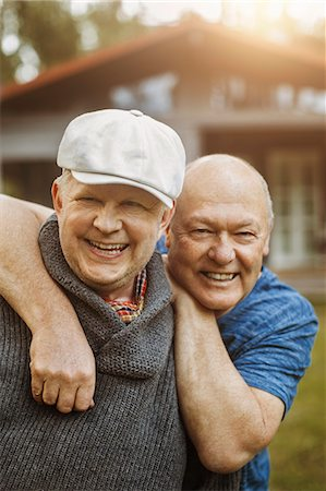 Portrait of happy gay man leaning on partner's shoulders at yard Stock Photo - Premium Royalty-Free, Code: 698-08330853