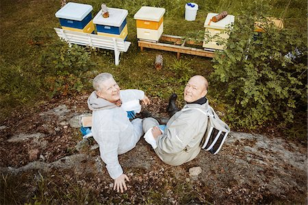 High angle portrait of happy beekeepers relaxing on field Stock Photo - Premium Royalty-Free, Code: 698-08330860