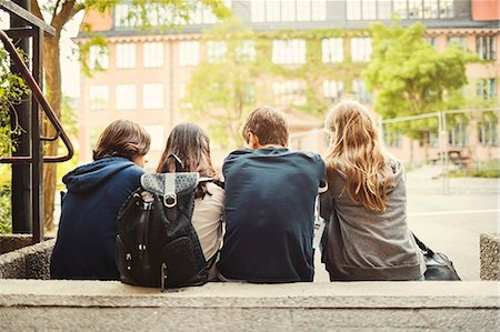 Rear view of teenagers sitting on steps outdoors Foto de stock - Sin royalties Premium, Código: 698-08331005