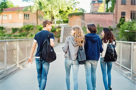 Rear view of teenagers talking while walking on bridge in city Foto de stock - Sin royalties Premium, Código: 698-08331024