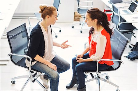 Mature businesswoman having discussion with female colleague in office Stock Photo - Premium Royalty-Free, Code: 698-08331085