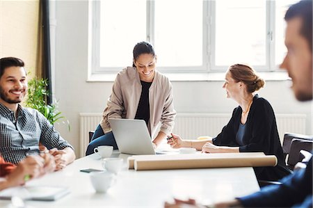 Happy businesswomen discussing over laptop in conference room Stock Photo - Premium Royalty-Free, Code: 698-08331137