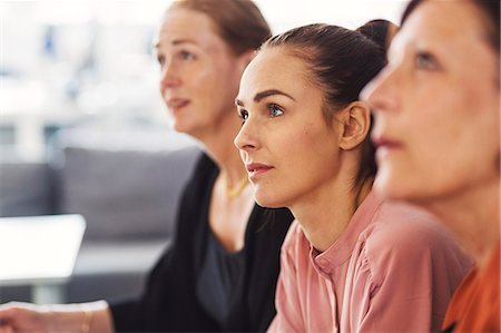 Concentrated businesswomen listening in meeting at office Stock Photo - Premium Royalty-Free, Code: 698-08331151