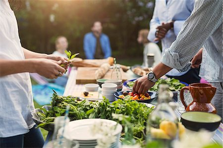 Midsection of friends preparing food at dining table in backyard Stock Photo - Premium Royalty-Free, Code: 698-08392999