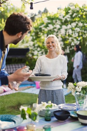 diversión - Happy young woman holding plates while looking at friend in yard during summer party Foto de stock - Sin royalties Premium, Código: 698-08393008