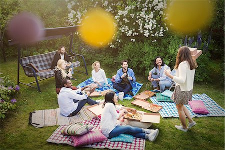 High angle view of friends having snacks during summer party at yard Stock Photo - Premium Royalty-Free, Code: 698-08393019