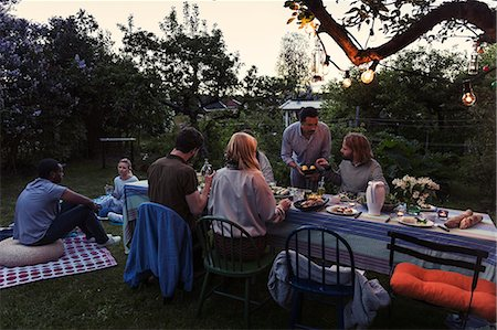 Friends having food during dinner party at yard Stock Photo - Premium Royalty-Free, Code: 698-08393020