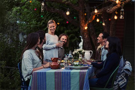 party - Happy woman talking to friends sitting at dinner table in yard Stock Photo - Premium Royalty-Free, Code: 698-08393023
