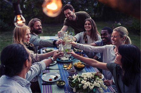 Happy multi-ethnic friends toasting drinks at dinner table in yard Stock Photo - Premium Royalty-Free, Code: 698-08393034