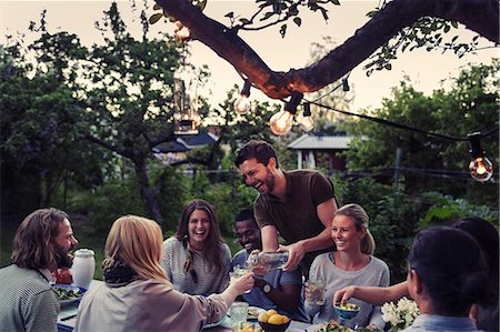 Happy man serving water to friend during dinner party at yard Stock Photo - Premium Royalty-Free, Code: 698-08393035