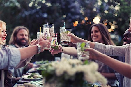 Multi-ethnic friends toasting mojito glasses at dinner table in yard Stock Photo - Premium Royalty-Free, Code: 698-08393030
