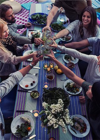 party - High angle view of multi-ethnic friends toasting drinks at dinner table in yard Stock Photo - Premium Royalty-Free, Code: 698-08393033