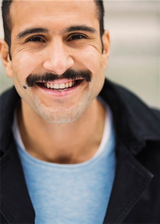 Portrait of young man smiling at tram station Stock Photo - Premium Royalty-Free, Code: 698-08393158