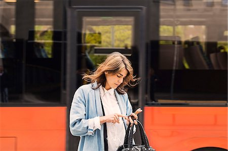 Young woman using mobile phone against bus Stock Photo - Premium Royalty-Free, Code: 698-08393196