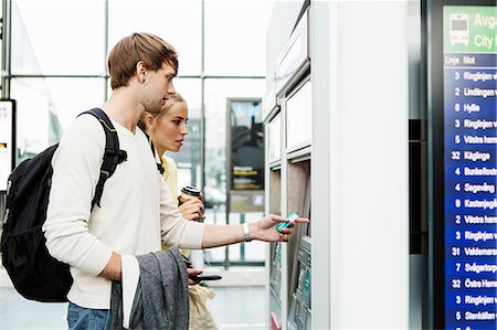 Friends standing by ATM at railroad station Stock Photo - Premium Royalty-Free, Code: 698-08393220