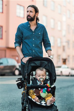Mid adult man pushing baby in carriage on sidewalk Stock Photo - Premium Royalty-Free, Code: 698-08393254