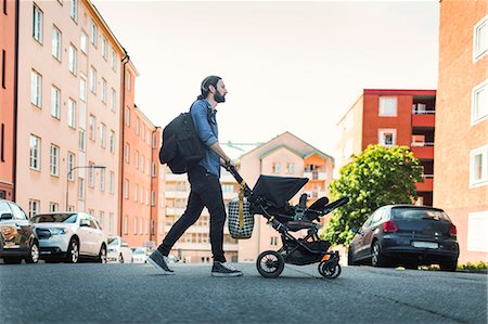 Full length side view of man pushing baby in carriage crossing city street Stock Photo - Premium Royalty-Free, Code: 698-08393257