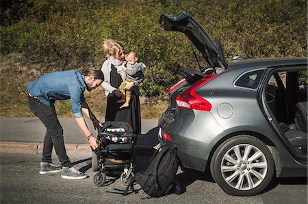 Mid adult parents with son and baby carriage near car on street Stock Photo - Premium Royalty-Free, Code: 698-08393251