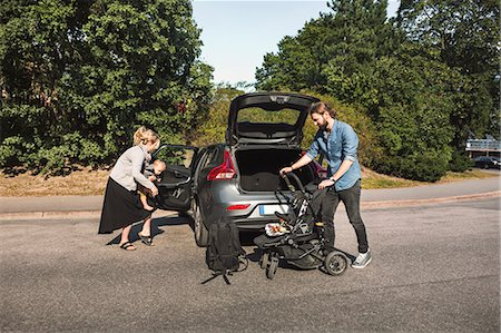 Mid adult parents with son and baby stroller near car on street Stock Photo - Premium Royalty-Free, Code: 698-08393252