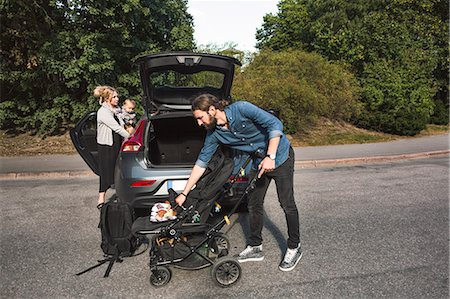 Mid adult parents with baby boy and stroller near car on street Stock Photo - Premium Royalty-Free, Code: 698-08393253