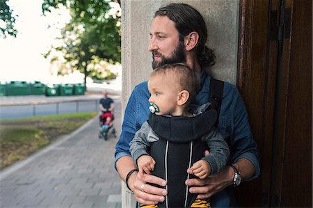 Thoughtful mid adult man carrying baby boy in carrier at doorway Stock Photo - Premium Royalty-Free, Code: 698-08393276