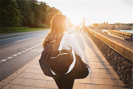 Rear view of female tourist walking on sidewalk of bridge Stock Photo - Premium Royalty-Free, Code: 698-08393318