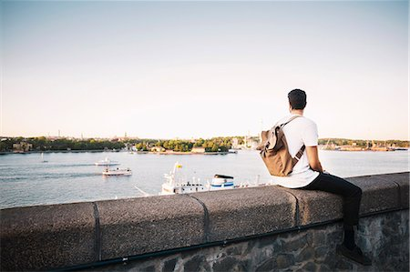 Male tourist looking at view while sitting on retaining wall of bridge against clear sky Stock Photo - Premium Royalty-Free, Code: 698-08393311