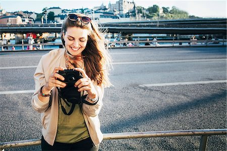Happy tourist holding camera on bridge against clear sky Stock Photo - Premium Royalty-Free, Code: 698-08393325