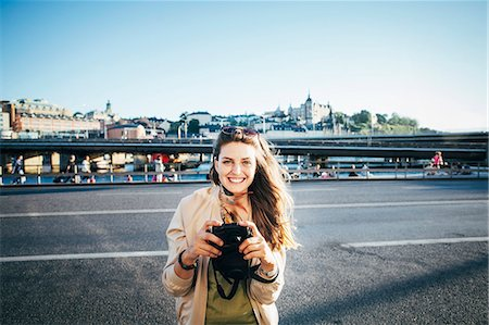 stock photograph - Portrait of happy tourist holding camera on bridge against clear sky Stock Photo - Premium Royalty-Free, Code: 698-08393327